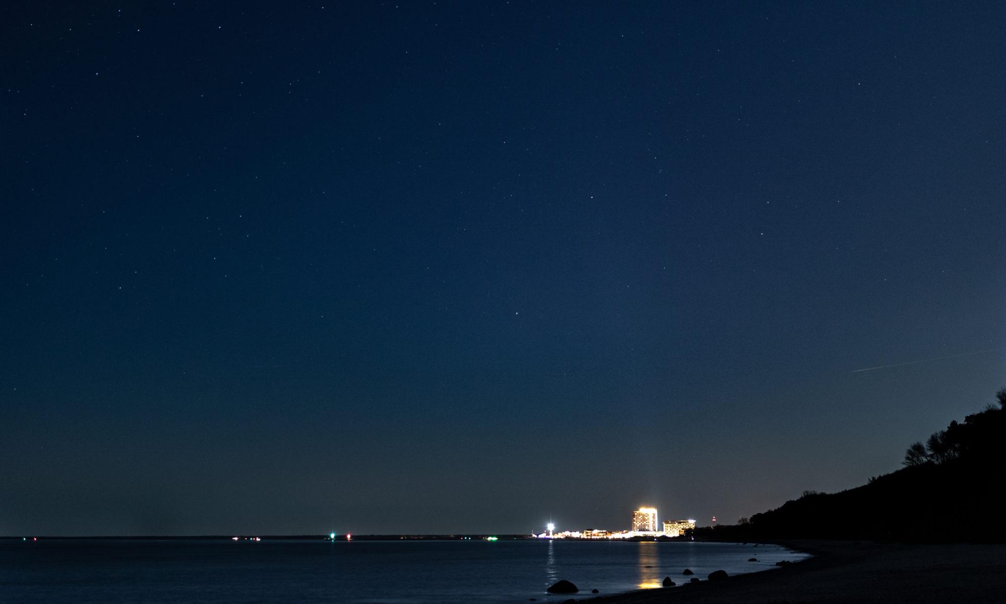 Das Foto zeigt Warnemünde nachts mit Sternenhimmel